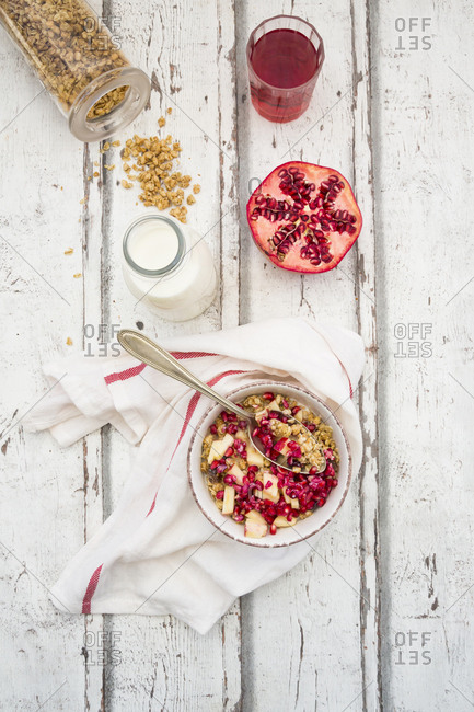 Breakfast with fruit muesli with pomegranate seed- bottle of milk and glass of pomegranate juice