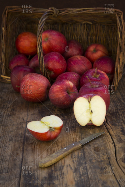 Red apples in basket- knife and halved on wood