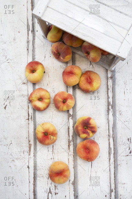 Doughnut peaches- wooden box on white wood