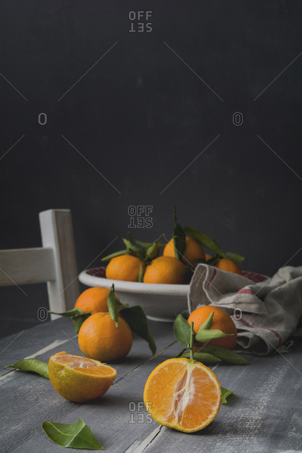 Sliced and whole tangerines on wooden table