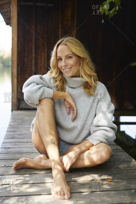 Smiling relaxed woman sitting on wooden jetty at a lake