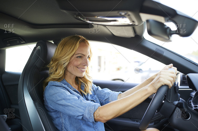 Smiling woman driving car - Offset