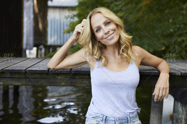 Smiling relaxed woman at wooden jetty at a lake