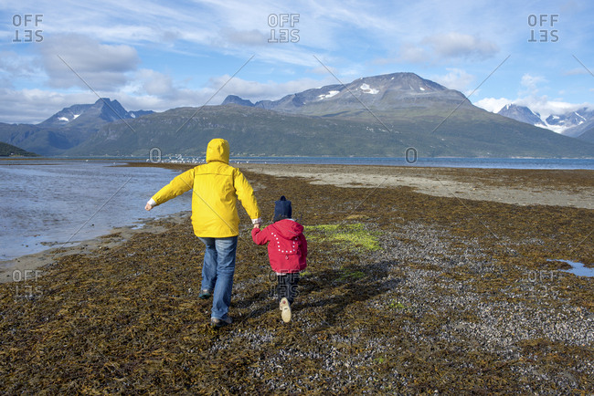 Norway- mother and daughter running at the beach- Lyngen fjord