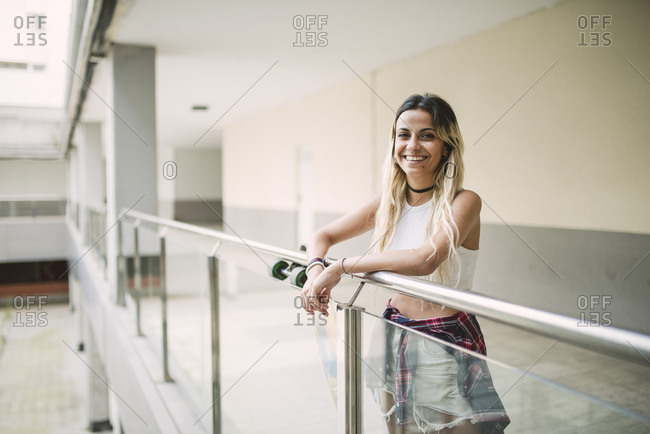 Smiling young woman leaning on railing- portrait
