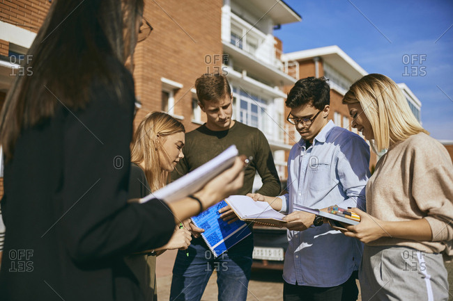 Group of students standing outdoors with documents