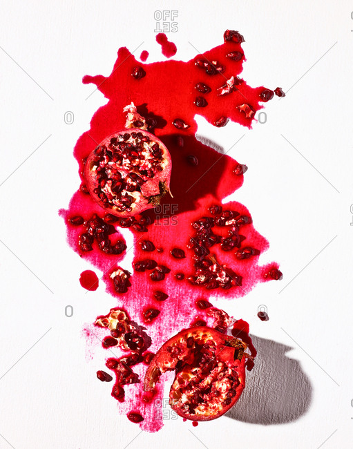 Pomegranate with juicy mess on white background