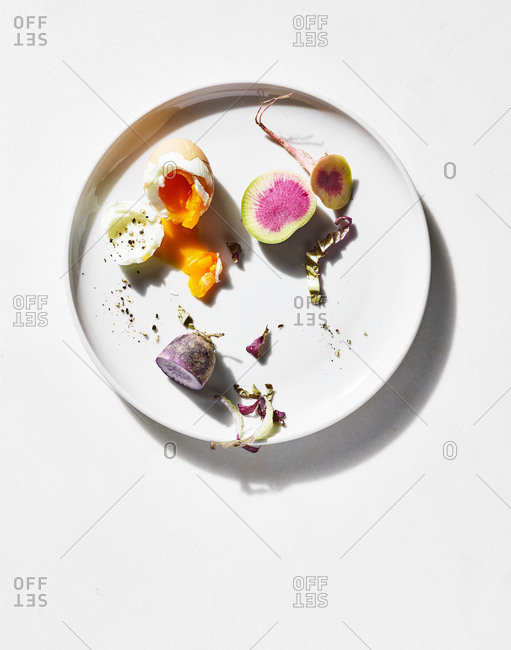 Soft boiled egg and radish pieces on plate