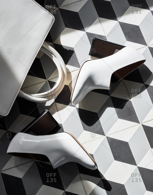 White heels and leather bag on geometric background