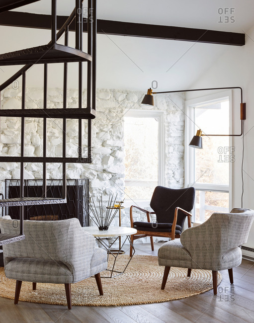 Three chairs by fireplace and winding staircase