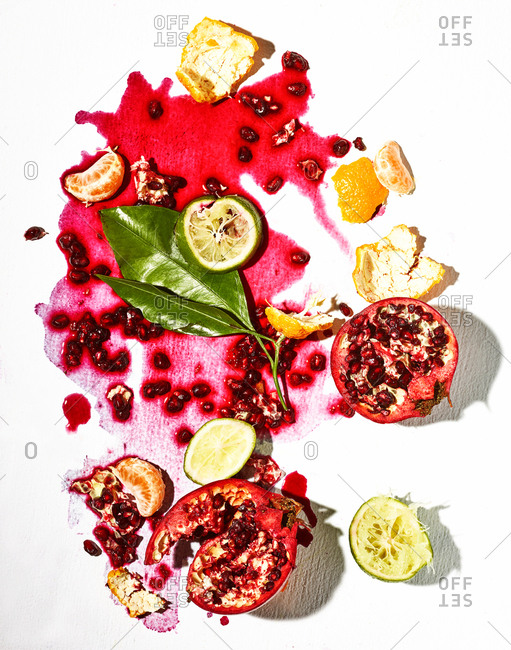 Pomegranate and citrus fruits with juice on white background
