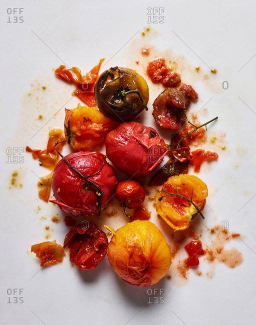 Red and yellow tomatoes on messy white background