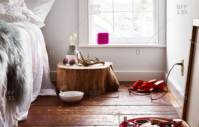 Red sandals on floor beside log bedside table with antlers