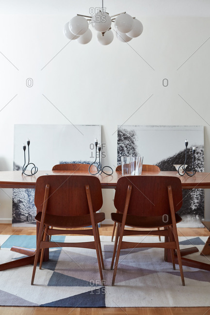 March 18, 2017 - Dining room with modern dining table, hanging lamp, and artwork