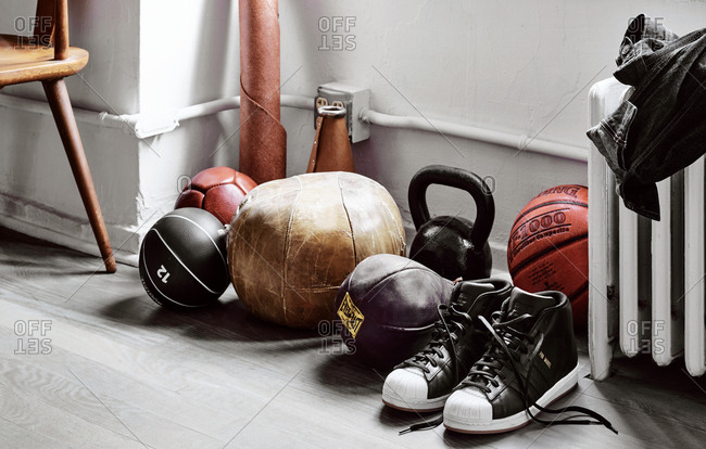 March 16, 2018 - Spalding basketball, Everlast punching bag, and Adidas Pro Model running shoes on the floor alongside other balls and athletic equipment