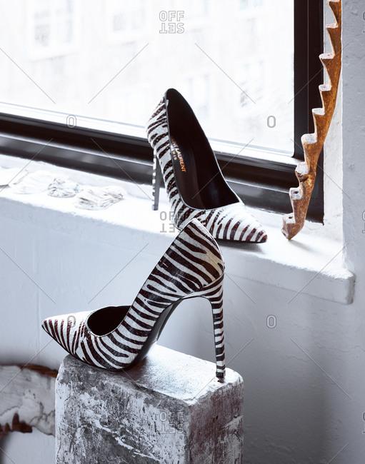 December 21, 2017 - Pair of Saint Laurent zebra print pumps displayed by a window
