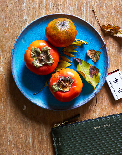 November 21, 2018 - Comme des Garcons embossed leather wallet on a table with a plate of persimmons and a matchbox