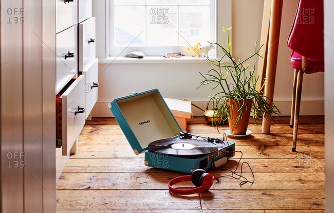 April 19, 2018 - Crosley Cruiser Deluxe portable turntable on hardwood floor in vintage living room