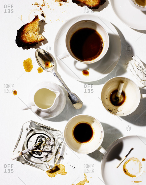 January 23, 2018 - Table with cigarettes in dirty coffee cup and an ashtray
