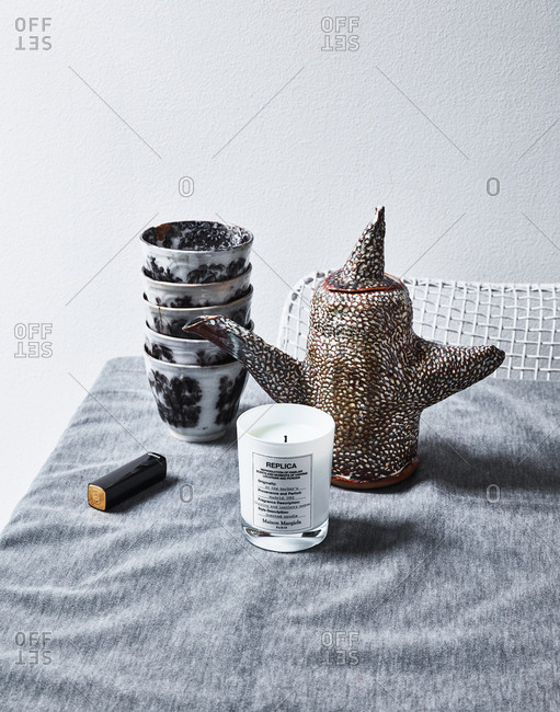 October 23, 2017 - Maison Margiela Replica scented candle and box of Chanel lipstick on table with artistic handmade teapot and a stack of traditional teacups