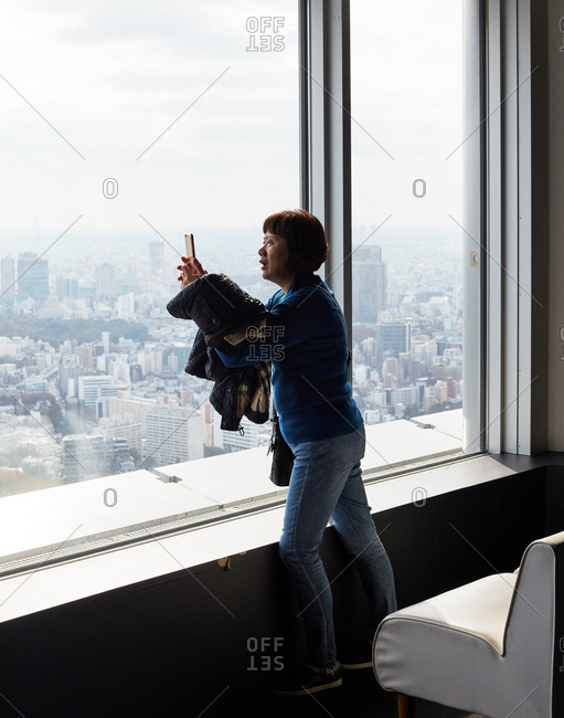 Tokyo, Japan - November 17, 2018: Woman using her phone to take a picture of the city outside of a window