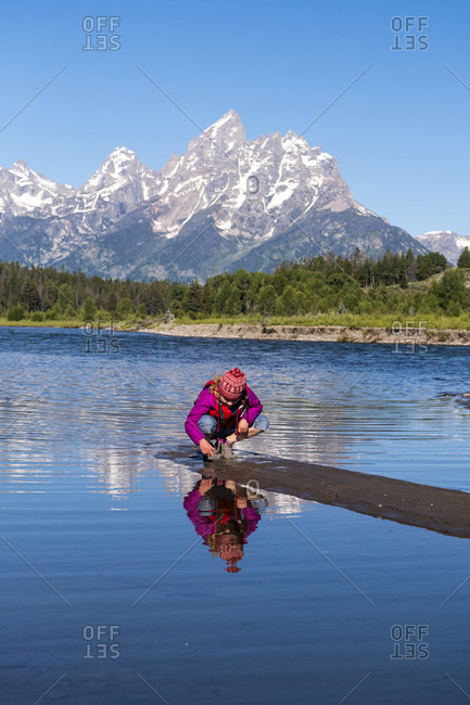 A young girl playing on a sandbar while canoeing the Snake River below the Grand Teton, Grand Teton National Park, Jackson, Wyoming, USA
