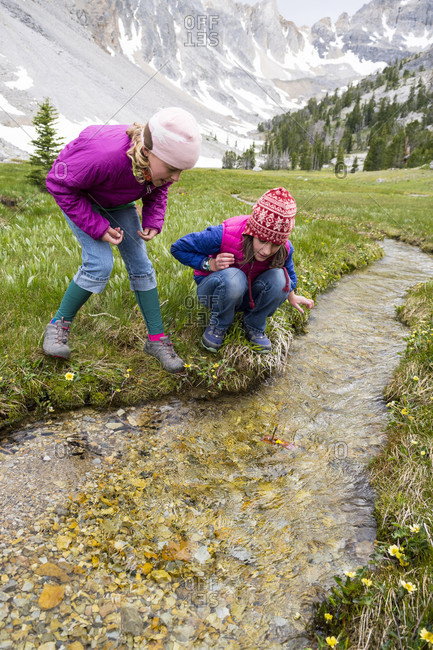 Two girls playing with toy boats in stream, Merriam Lake Basin, Upper���Pashimeroi���Valley, Lost River Range, Challis, Idaho, USA