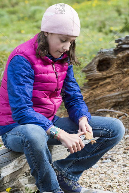 A young girl whittling a stick in the Merriam Lake Basin, Upper Pashimeroi Valley, Lost River Range, Challis, Idaho, USA