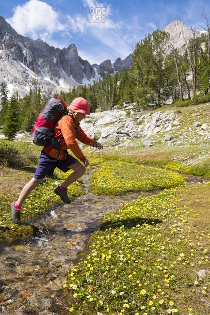 A young girl jumping across a stream while hiking in the Merriam Lake Basin, Upper Pashimeroi Valley, Lost River Range, Challis, Idaho, USA