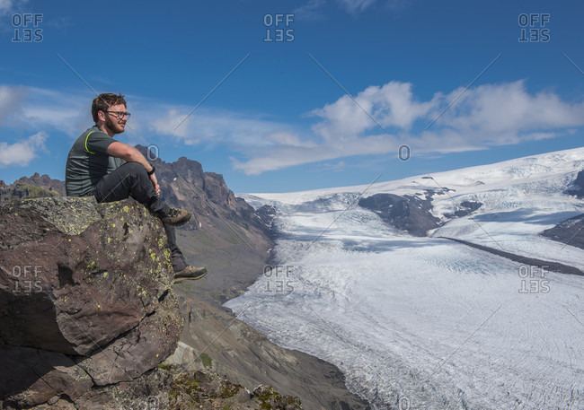 Side view shot of a mid adult male hiker sitting on a rock near the���Skaftafellsjokull���glacier,���Vatnajokull���National Park, Iceland
