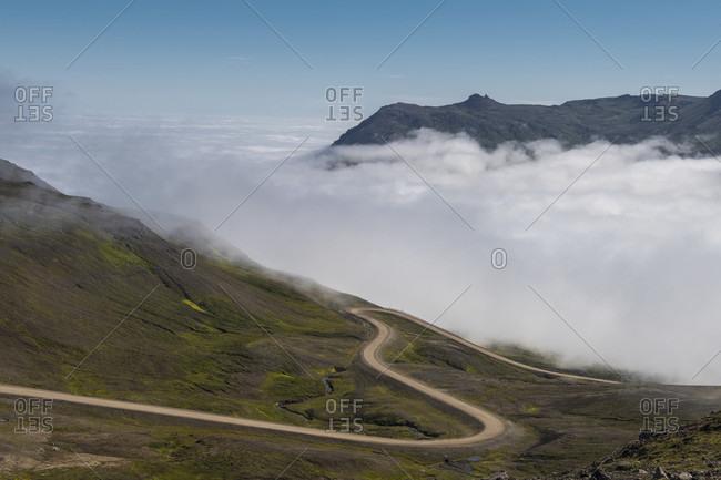 Scenic landscape with a road on hillside and a fog at���Borgafjordur���Eystri, Iceland