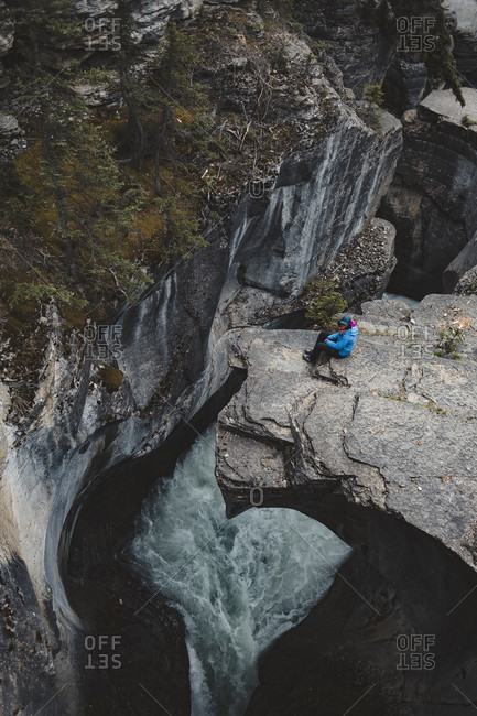 Female hiker sitting at edge of cliff of Mistaya���Canyon with���Mistaya���River flowing underneath, Alberta, Canada