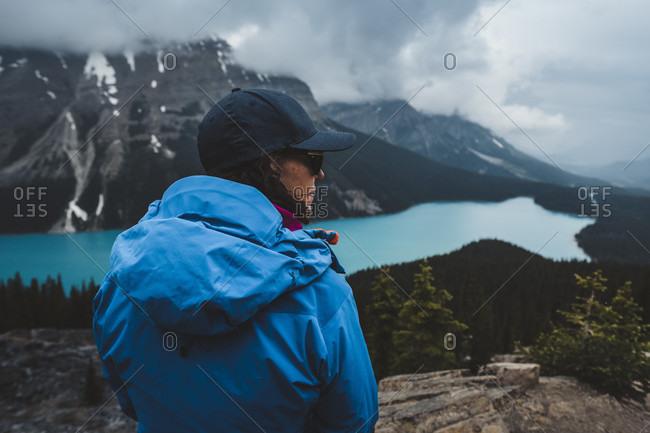 Female hiker wearing baseball cap and blue jacket admiring scenic view of���Peyto���Lake and surrounding landscape, Alberta, Canada