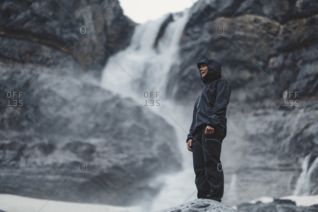 Female hiker wearing hooded jacket standing against Bow Falls waterfall in Bow Valley, Alberta, Canada