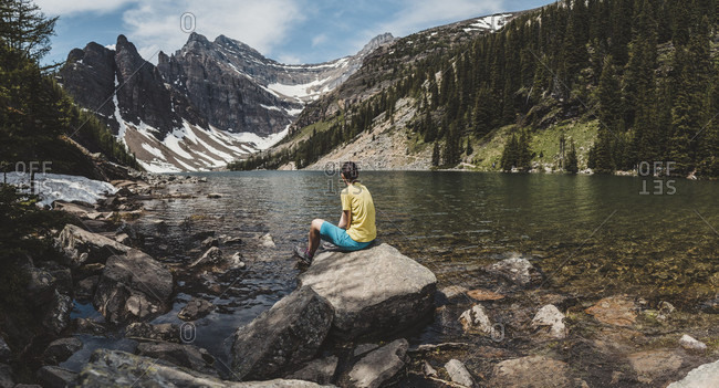 Female hiker sitting on lakeshore rock of Lake Agnes and admiring scenic mountain landscape, Alberta, Canada