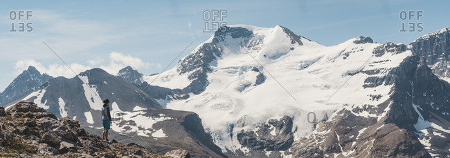 Female hiker admiring scenic view of Athabasca peak and glacier���from Wilcox Pass, Alberta, Canada