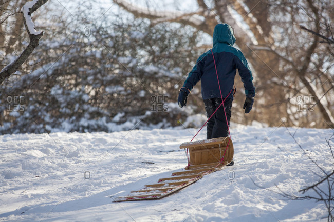 Ten year old boy pulling empty sled up snowy hill,���Marblehead, Massachusetts, USA