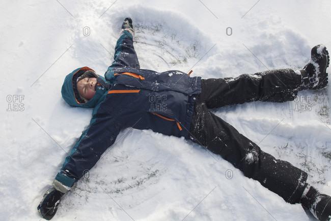 Ten year old boy making snow angel,���Marblehead, Massachusetts, USA