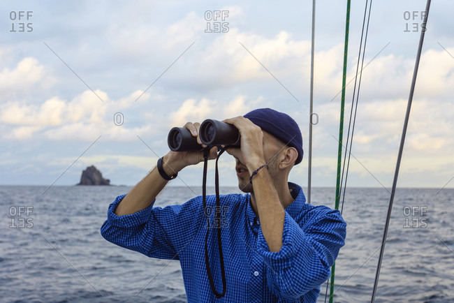 Head and shoulders shot of a man looking through binoculars on a sailboat in sea, Lombok, Indonesia