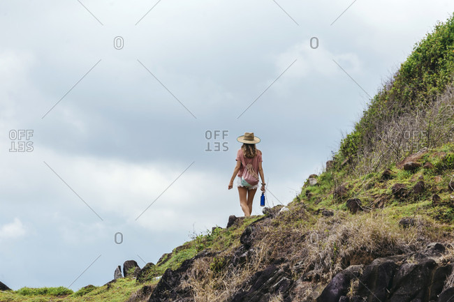 Rear view shot of female tourist walking in natural setting,���Kuta,���Lombok, Indonesia