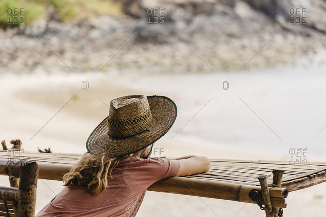 Rear view of female tourist in straw hat looking at sea from beach, Bali, Indonesia