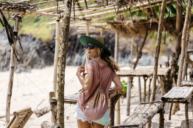 Waist up shot of young woman with straw hat on beach, Kuta, Lombok, Indonesia