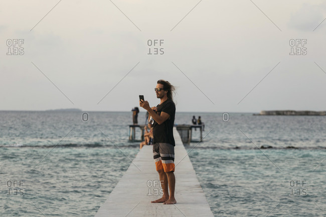 Side view shot of a single male tourist taking a picture on a pier,���Thulusdhoo, Male, Maldives