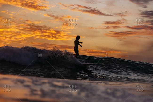 Silhouette of male surfer riding wave in sea at sunset,ÔøΩÔøΩÔøΩChanggu, Bali, Indonesia