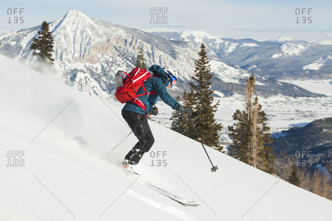 Side view shot of a single woman skiing down Mount Emmons, Gunnison National Forest, Colorado, USA