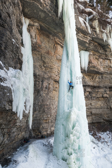 Male ice climber ascending ice pinnacle at Rigid Designator Amphitheater, Vail, Colorado, USA
