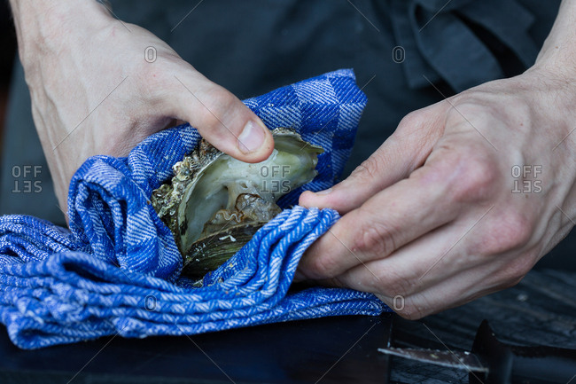 Close-up of hands shucking oysters