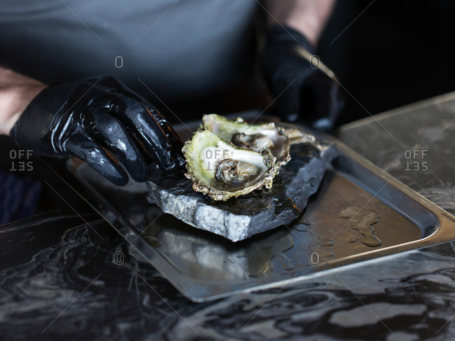 Person preparing oysters on a metal tray