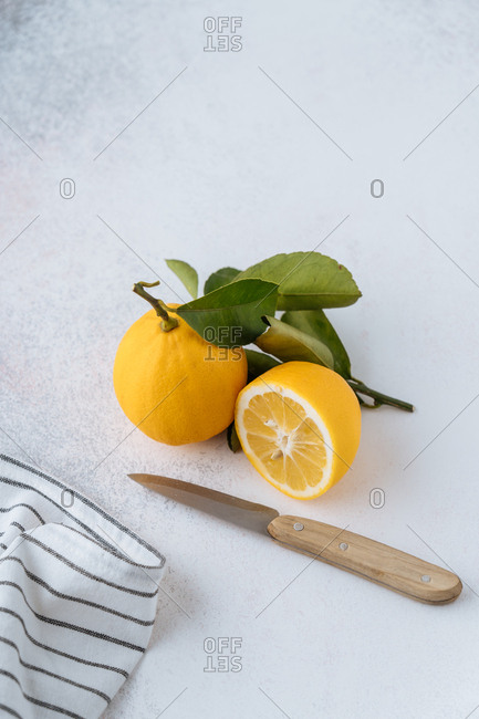 Lemons and knife on countertop with striped cloth