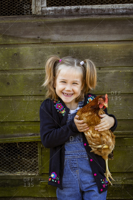 Smiling girl holding chicken, looking at camera.